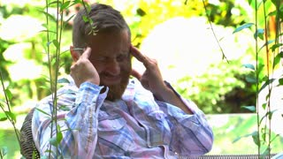 Man sitting in the exotic garden and having painful headache