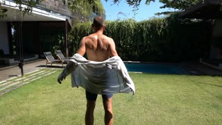 Man standing in his garden and puts shirt on, slow motion shot at 240fps, steady