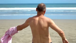 Man standing on the beach and takes shirt off, slow motion shot at 240fps, stead