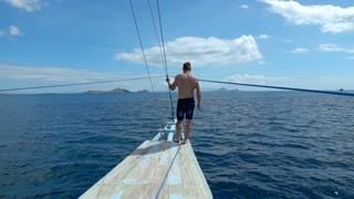 Man standing on the ship's bow, slow motion shot at 240fps, steadycam shot