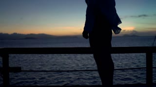 Man standing on the wind and admires the sunset, steadycam shot, slow motion sho