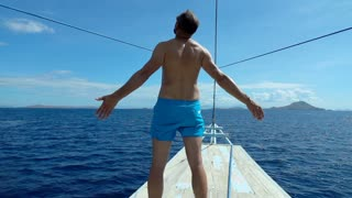 Man standing on the yacht and feels free, slow motion shot at 240fps, steadycam