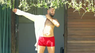 Man standing outside and puts on shirt, steadycam shot, slow motion shot at 240f