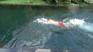 Man swimming in the pool, slow motion shot at 240fps, steadycam shot