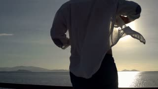 Man takes shirt off and admires the view, steadycam shot, slow motion shot at 24
