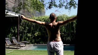 Man walking outside and relaxing in the garden, steadycam shot, slow motion shot