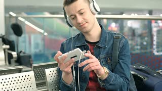 Man watching something funny on smartphone while sitting on the train station, s