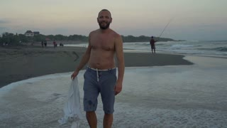 Man waving with a shirt on the beach and smiling to the camera, steadycam shot,
