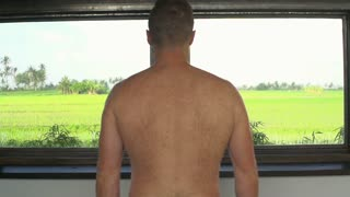 Man with naked back walking to the window and opens it, steadycam shot, slow mot