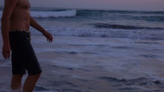 Man with naked torso walking on the beach, slow motion shot at 240fps, steadycam