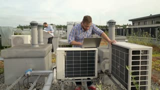 Men working on the air condition on the roof, steadycam shot