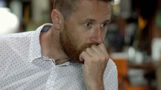 Pensive man sitting in restaurant and looks worried, close up, steadycam shot