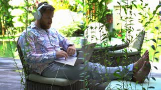 Pensive man wearing headphones and having a videocall on laptop