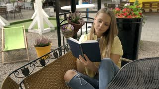 Pretty blonde girl reading absorbing book and smiling to the camera