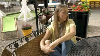 Pretty blonde girl sitting in the outdoor cafe and looks very worried