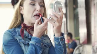 Pretty girl applying red lipstick while sitting in the outdoor cafe, steadycam s