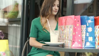 Pretty girl checking her new red skirt in the outdoor cafe, steadycam shot