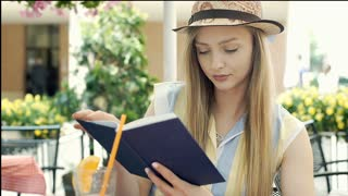 Pretty girl drinking fresh orange juice and reading book in the cafe, steadycam