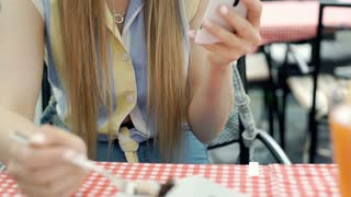 Pretty girl eating tasty dessert and texting messages on smartphone, steadycam s