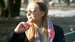 Pretty girl enjoys sun in the park and wearing stylish sunglasses