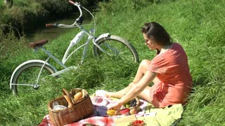 Pretty girl having a picnic on countryside and drinking fresh orange juice, stea