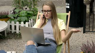 Pretty girl holding modern notebook and talking on cellphone