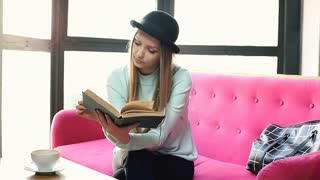 Pretty girl in bowler hat drinking coffee and reading book on the pink couch