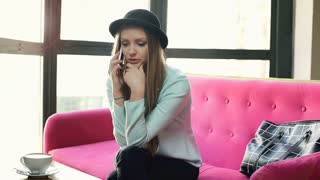 Pretty girl in bowler hat having a quarrel while speaking on cellphone