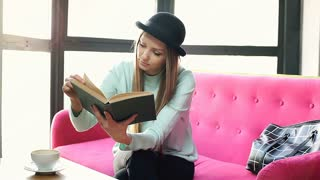 Pretty girl in bowler hat sitting on the pink couch and reading book