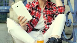 Pretty girl in checked shirt wearing rollerblades and doing selfies on tablet, s