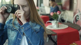 Pretty girl in denim jacket and with red lips doing photos on old camera, steady