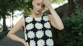 Pretty girl in floral shirt looks dissatisfied while having headache, steadycam
