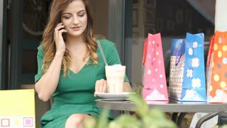 Pretty girl in green dress sitting in the outdoor cafe and chatting on cellphone