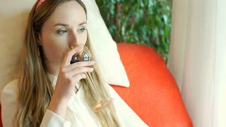 Pretty girl leaning on the pillow and drinking wine while smiling to the camera, steadycam shot