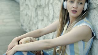 Pretty girl listening music while leaning on the brick wall and looks sad, stead