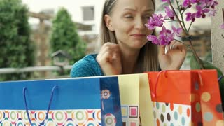 Pretty girl looks excited while checking her shopping bags, steadycam shot