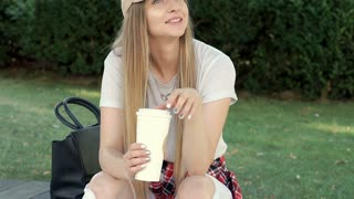Pretty girl looks happy while relaxing in the park and drinking coffee, steadyca