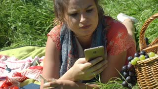 Pretty girl looks shocked after checking message on smartphone, steadycam shot