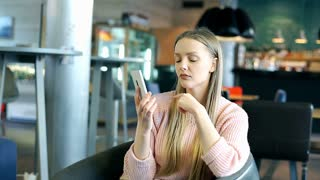 Pretty girl looks surprised while receiving good news on cellphone