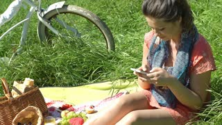 Pretty girl relaxing on the blanket and texting message on smartphone, steadycam