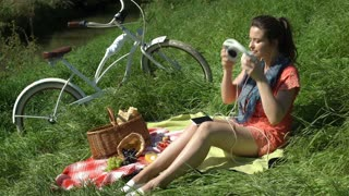 Pretty girl relaxing on the blanket on countryside and listening music, steadyca