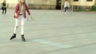 Pretty girl riding on rollerblades and listening music on headphones, steadycam
