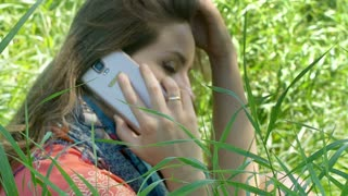Pretty girl sitting in the grass and talking on cellphone, steadycam shot