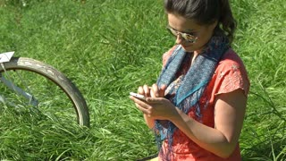 Pretty girl sitting on blanket and browsing internet on smartphone, steadycam sh