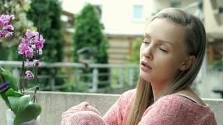Pretty girl sitting on terrace and looks very sad, steadycam shot