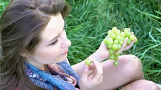 Pretty girl sitting on the grass and eating grapes, steadycam shot
