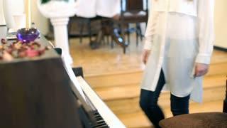 Pretty girl starts to play the piano and looks happy, steadycam shot