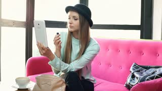 Pretty girl using tablet as a mirror while painting her lips in the cafe