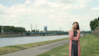 Pretty girl walking on boulevards next to the river and chatting on cellphone, s