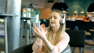 Pretty girl wearing headphones and talking on cellphone with someone